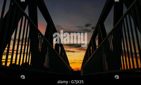 A dramatic sky behind a pedestrian footbridge over the A12 road Wanstead, London E11 - Stock Photo