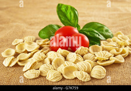 Orecchiette tomatoes and basil on jute - Stock Photo