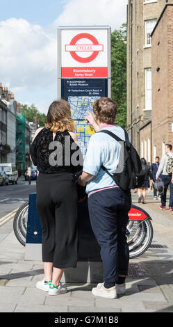A couple reading a Santander kiosk noticeboard in Bloomsbury in London England, UK - Stock Photo