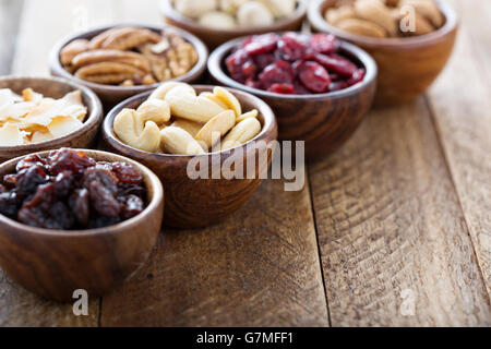 Variety of nuts and dried fruits in small bowls - Stock Photo
