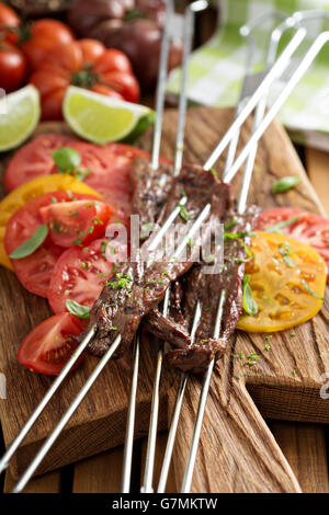Flank steak on skewers with tomatoes - Stock Photo