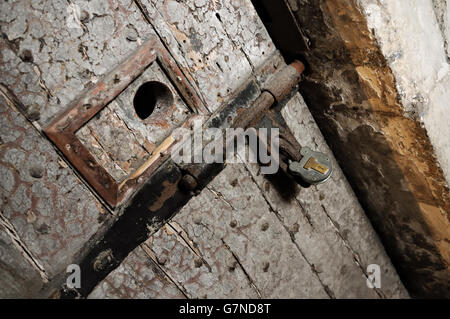 Old door with peephole and padlock at Kilmainham Gaol in Dublin, Ireland - Stock Photo