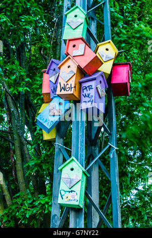 Multicoloured birdboxes on a metal street pole in a park in Copenhagen. - Stock Photo