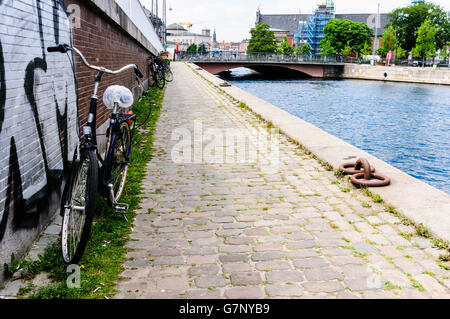 Bicycle parked along a path beside a canal in Copenhagen, Denmark - Stock Photo