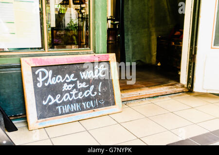 Sign outside a restaurant saying 'Please wait to be seated! Thank you!' - Stock Photo