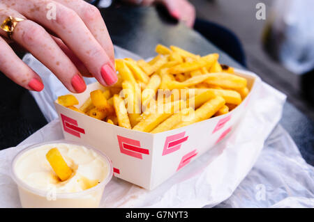 A woman takes a fry from a box of French Fries beside a tub of mayonnaise. - Stock Photo