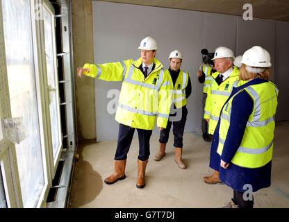 Prime Minister David Cameron views building work nearing completion with crest Building CEO Steve Stone (third left), - Stock Photo