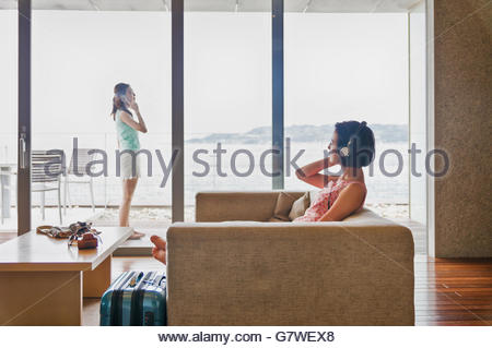 A woman listening to music and another woman talking on the phone - Stock Photo