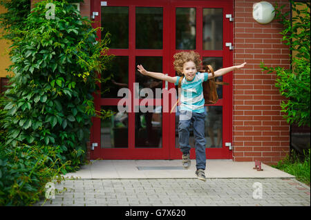 The little first grader rejoices to the beginning of summer vacation. He runs out from doors of school. As if flies. - Stock Photo
