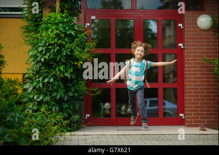 The carefree first grader rejoices to the beginning of summer vacation. He runs out from doors of school. As if - Stock Photo