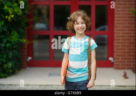 The little schoolboy stand on a schoolyard and joyfully smiles. The curly boy with a nice face. Behind the school - Stock Photo