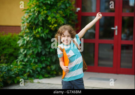 The schoolboy rejoices to the termination of academic year and the beginning of summer vacation. The boy has raised - Stock Photo