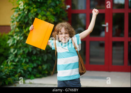 The schoolboy rejoices to the termination of academic year and the beginning of summer vacation. The fellow has - Stock Photo