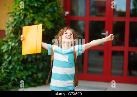 The little school student rejoices to the termination of academic year and the beginning of summer vacation. The - Stock Photo