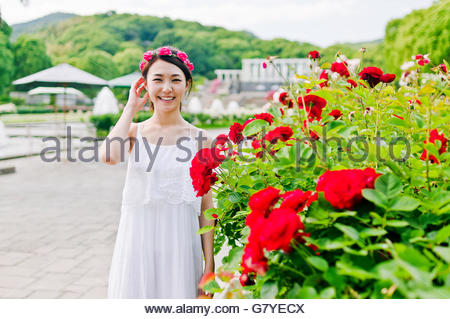 Woman standing in front of flower - Stock Photo