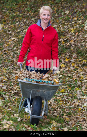 Gardening, woman pushing a wheelbarrow full of leaves