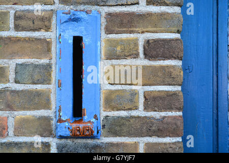 Close up of old blue mailbox in a bricks wall - Stock Photo