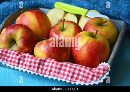 close up of red, yellow ,green apples in wooden bowl with knife and apple slices red white nostalgic countryside - Stock Photo
