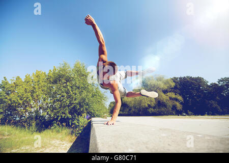 sporty young man jumping in summer park - Stock Photo