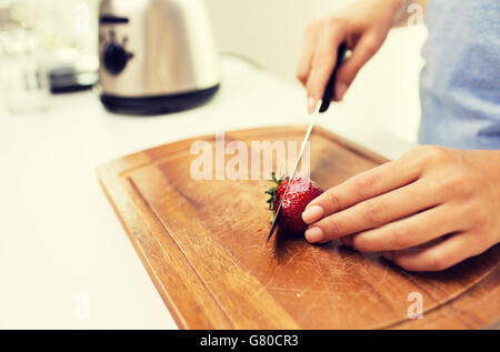 close up of woman chopping strawberry at home