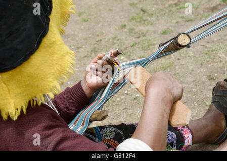 Peruvian woman in traditional clothing weaving cloth on a hand loom in the Andes Mountains, Peru - Stock Photo