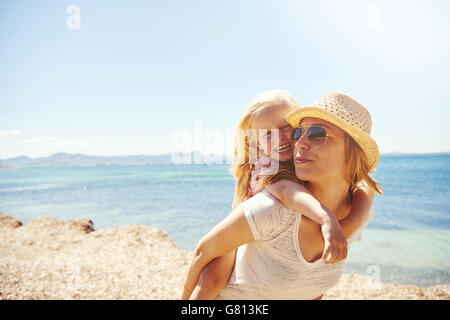 Laughing vivacious little blond girl with her mother at the beach riding on her in a piggy back on a rocky shore, - Stock Photo