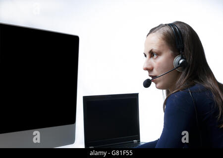Young girl wearing headset in fornt of two monitors at a Public Safety Answering Point - Stock Photo