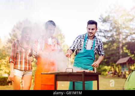 Friends having a barbecue party in nature  while having a blast - Stock Photo