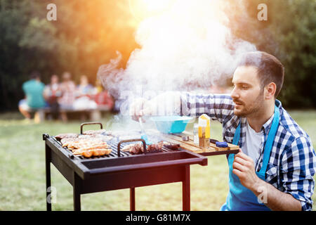 Barbecue in nature being done by friends - Stock Photo