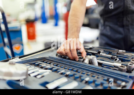 Car mechanic selecting the right tool for the job - Stock Photo