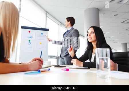 Workers at business meeting looking at presentation of financial reports in modern office - Stock Photo