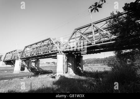 Railway train tracks steel bridge structure at river crossing closeup photo of infrastructure. - Stock Photo