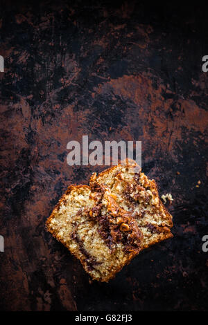 Top view of two pieces of banana bread with nutella swirl and chopped hazelnuts on dark background.  Dark food photography. - Stock Photo