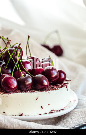 Bavarian mousse cake with cherries and dark chocolate on top. Made with cream cheese and whipped cream. - Stock Photo