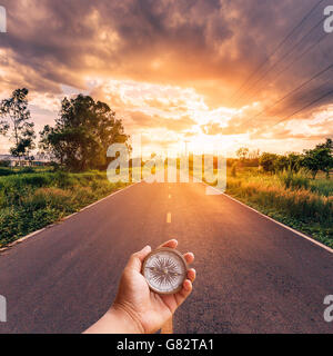 Hand man holding compass on road with sky sunset. - Stock Photo
