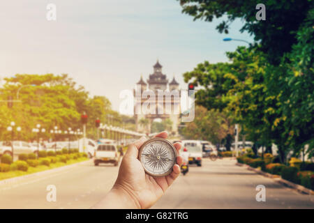 Hand man holding compass on road Victory Gate Patuxai, Vientiane, Laos, Southeast Asia - Stock Photo
