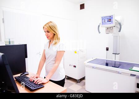 Veterinarian in white uniform at veteringary clinic working - Stock Photo