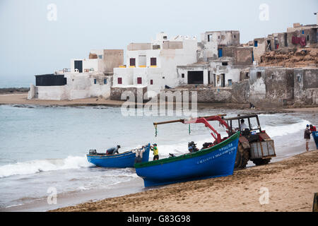 A tractor helps lift fishermen's boats ashore in Tifnit beach near Agadir, Morocco. - Stock Photo