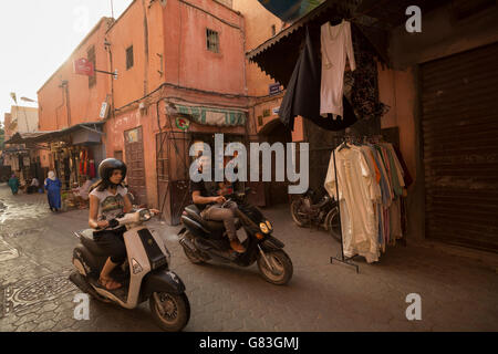 Local residents and tourists dash through the narrow streets of the Marrakesh Medina, Morocco. - Stock Photo