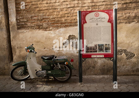 A cultural site marker stands along a narrow street in the Marrakesh Medina, Morocco. - Stock Photo