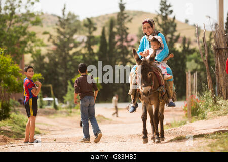 A woman and her young child ride a donkey down a dirt road in the village of Ben Khili, Morocco. - Stock Photo