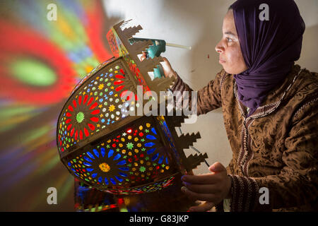 An artisan creates traditional lighting fixtures in her workshop in Fez, Morocco. - Stock Photo