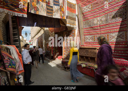 Local residents dash through the rug-lined narrow streets of the Fez Medina in Morocco. - Stock Photo