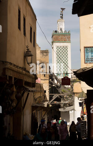 An ancient minaret towers over the streets of the old Medina of Fez, Morocco. - Stock Photo