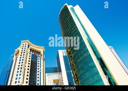 City centre West Bay area of Doha, Qatar. Majlis Al Taawon Street. Left is Burj Al Qassar Tower right is Olympic - Stock Photo