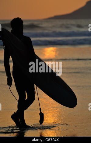 surfer and surfboard stroll on golden sands at sunset  in Wales - Stock Photo