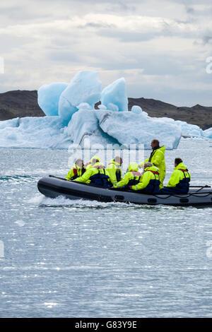 Tour group taken by boat to see icebergs on Jokulsarlon Lagoon, Iceland. - Stock Photo