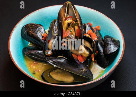 Delicious steamed mussels in turquoise plate - Stock Photo