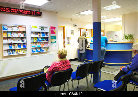Waiting room in a British GP practice with patients sitting and standing by reception desk waiting to register - Stock Photo