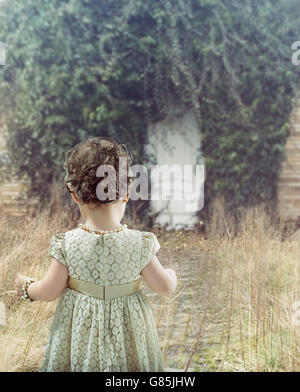 Little cute girl looking at white door - Stock Photo